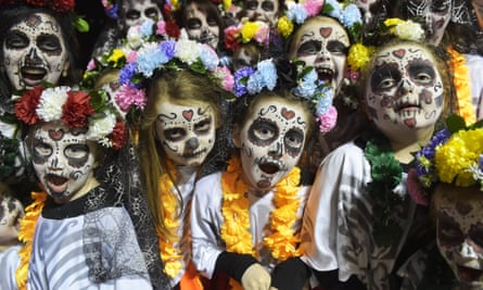 Children take part in the carnival in Derry, for Halloween, their faces painted as ghouls and zombies.