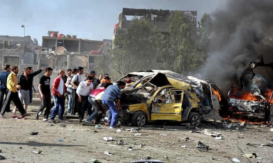 Locals rush to help victims of two suicide bombs in Damascus, Syria, May 2012