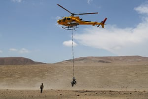 Stage 7: San Juan de Marcona to San Juan de Marcona, PeruThe Nomade Racing Motorbike of Charlie Herbst is lifted by the helicopter as he is taken away after being injured in the desert