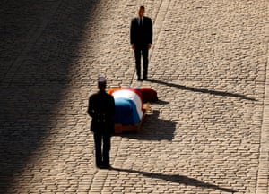 Emmanuel Macron stands behind the coffin of Charles Aznavour