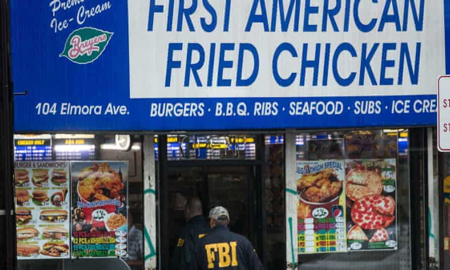 Members of the FBI and other law enforcement officials enter the fried chicken store in Elizabeth, New Jersey.