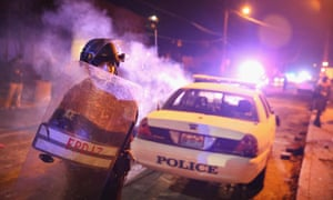 Police stand guard in front of a smouldering squad car after it was set on fire by demonstrators in Ferguson