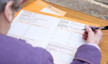 An unpaid carer fills in the carer's allowance form.