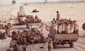 Captured Egyptian soldiers pass an Israeli troop convoy in the Sinai desert on 8 June 1967.