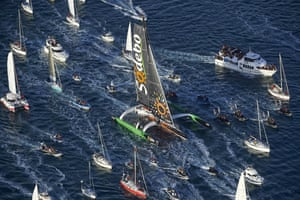 Sailors surround Thomas Coville's Sodebo trimaran as he approaches the port of Brest.