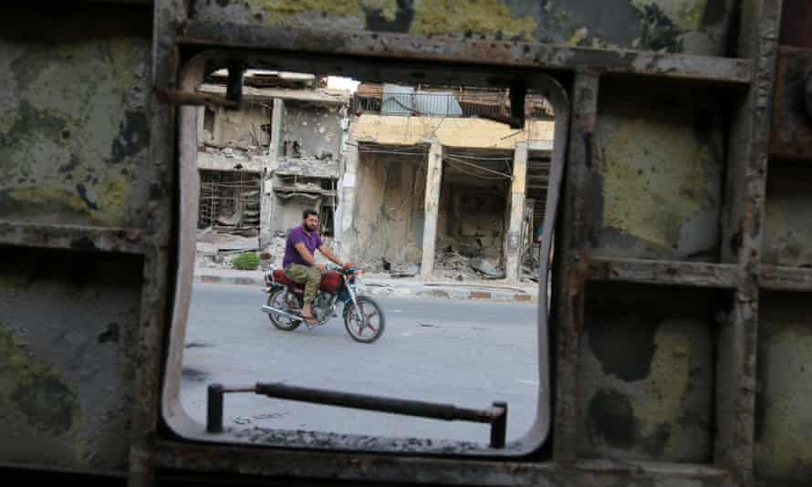 A man rides a motorcycle near damaged buildings in the rebel-held Old Aleppo where a ceasefire came into effect on Monday.