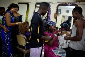 Young men who have come to Conakry's Miskaa Salon for cut price condoms are shown how to use them correctly by apprentice hairdresser Nene Diakité.