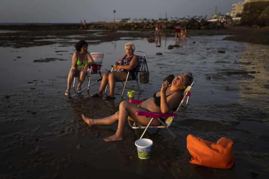 People sunbathe at sunset in a beach in Chipiona, a town and municipality located on the Atlantic coast in the province of Cadiz, Spain.
