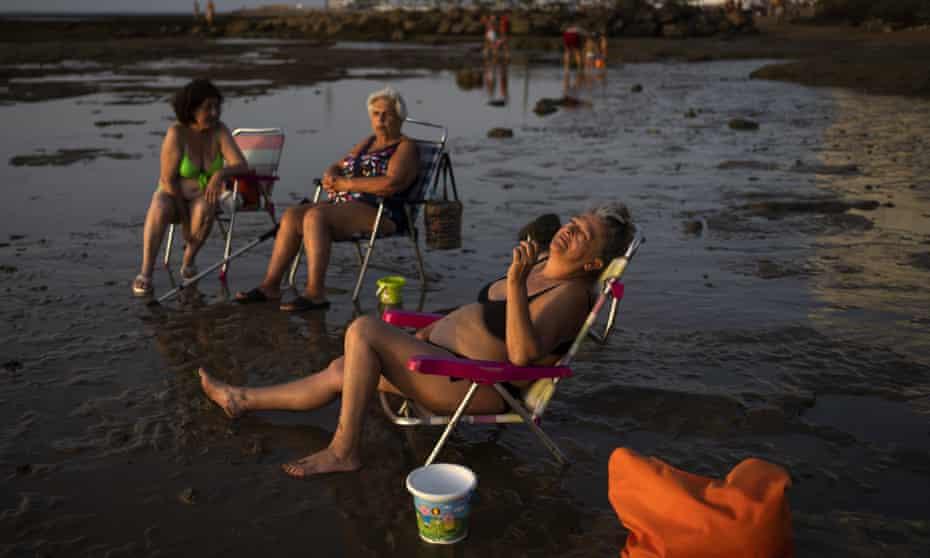 Sunbathers at a beach in Chipiona, Cádiz, Spain.