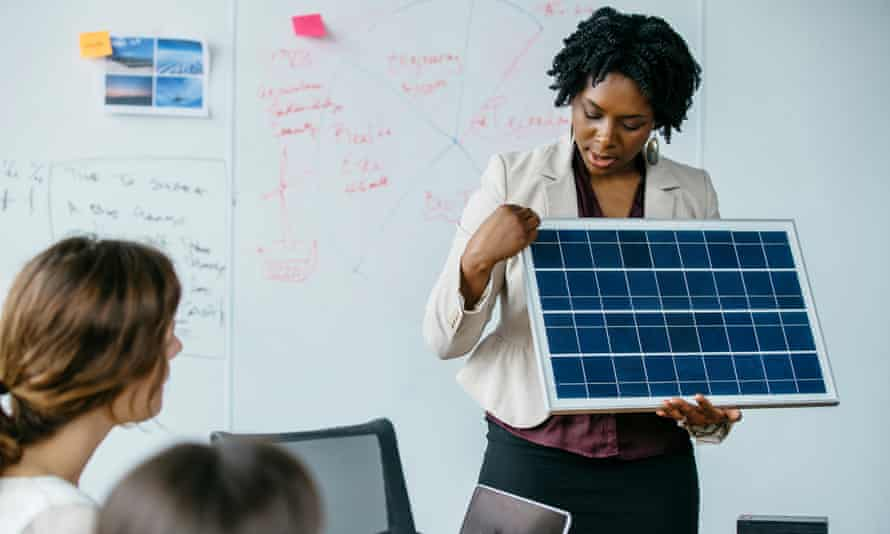 Businesswoman explaining solar panel model during meeting in office