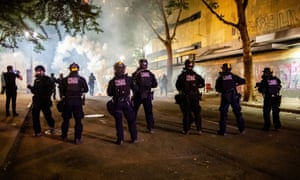 Federal agents stand in the street firing tear gas, pepper balls and other dispersants overnight on Tuesday.