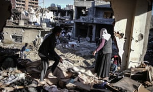 People carry their belongings from their ruined houses in Cizre.