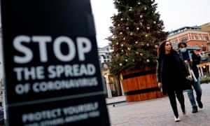 Pedestrians pass a coronavirus warning sign in Covent Garden in central London