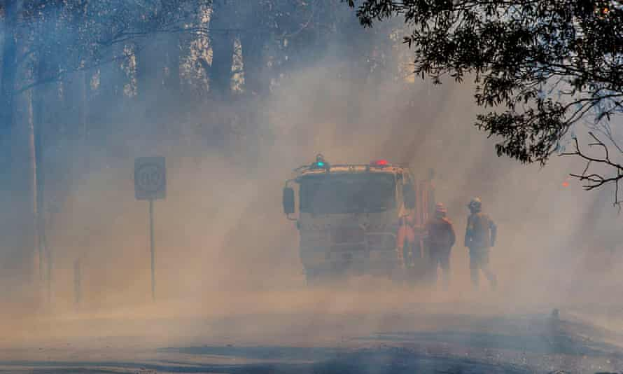 A firetruck pauses on a road in Hillville, NSW, where fires keep starting up because of flying embers