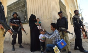 Pakistani policeman stand guard as a health worker administers polio drops to a child during a polio vaccination campaign in April 2016