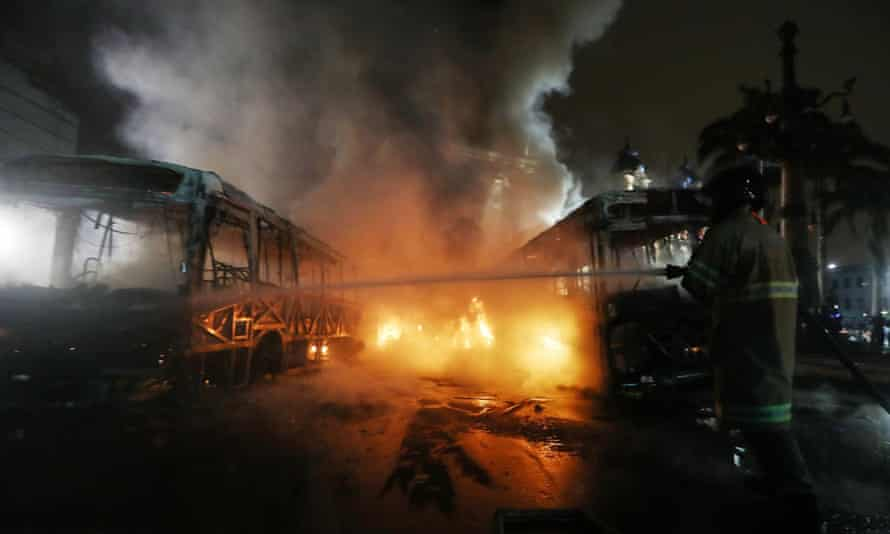 A firefighter works douses a burning bus in Rio.