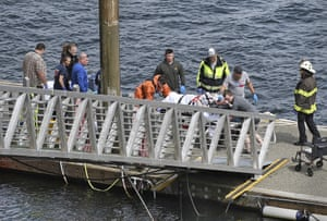 Emergency response crews transport an injured passenger to an ambulance at the George Inlet Lodge docks on Monday.