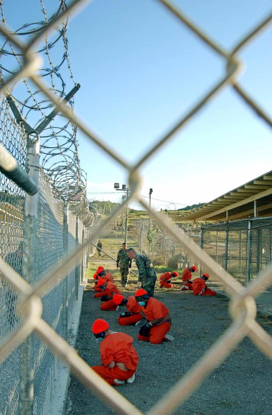 Detainees sit in a holding area under the surveillance of US military police at Guantánamo in January 2002.