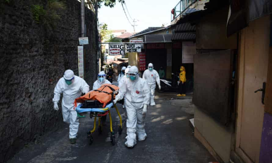 Health workers carry the body of a person who died with Covid-19 while isolating at home in Bandung, Indonesia.
