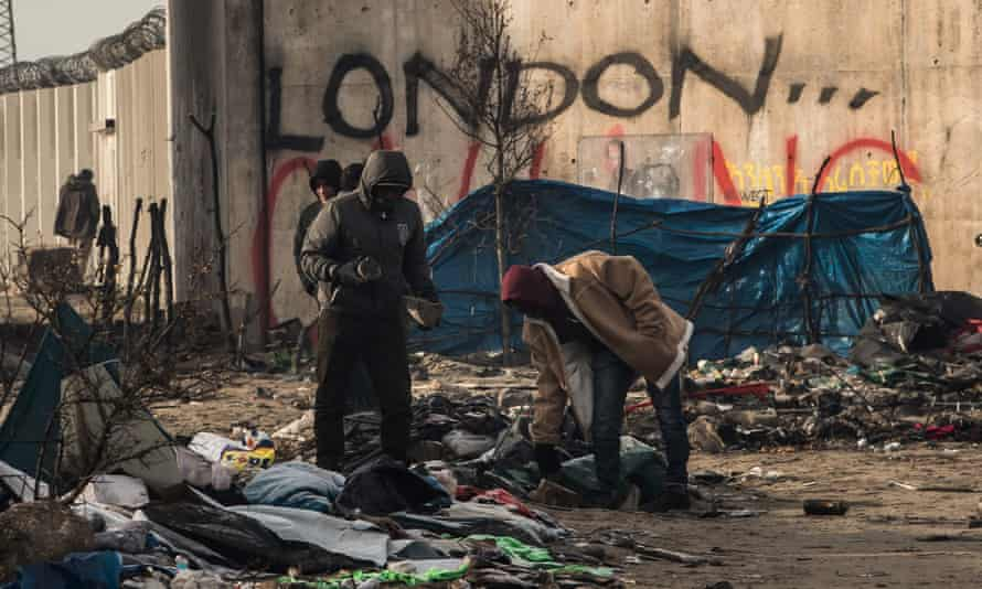 London calling? People pick through the remains of shelters in the dismantled part of the Jungle, cleared of some 1,500 people.