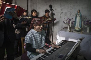A Chinese Catholic woman accompanies singers on the keyboard for a Palm Sunday mass at an underground church in Shijiazhuang, China