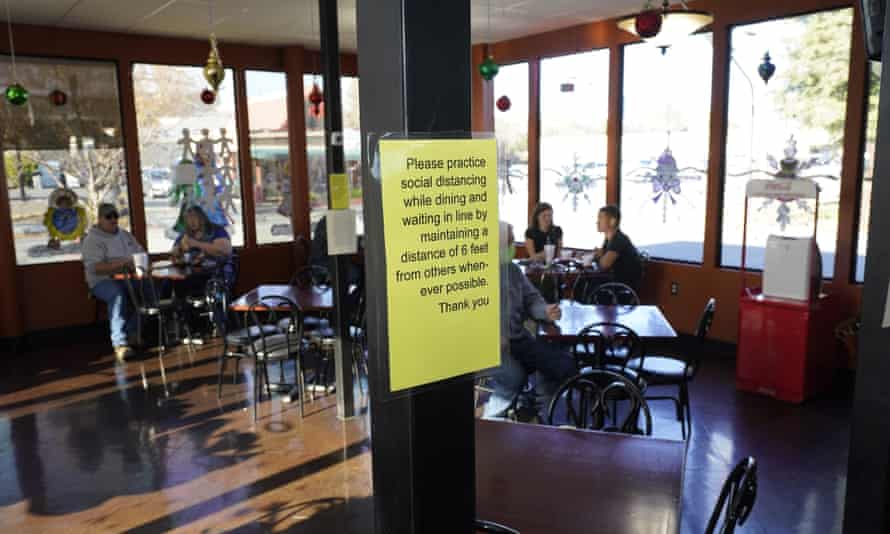 A sign advising patrons to maintain social distancing is posted in the indoor dining area of the San Francisco Deli in Redding, California.