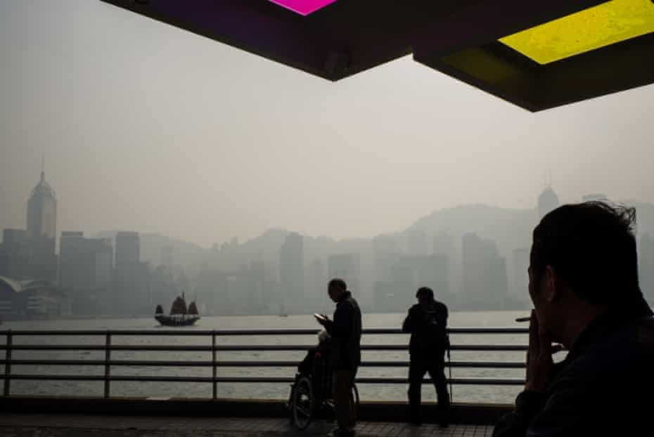 HONG KONG-WEATHER-POLLUTIONA man smokes a cigarette (R) at the Kowloon promenade as smog engulfs Hong Kong's famous skyline on January 22, 2018. Hong Kong's famous skyline was engulfed in smog on January 22, with residents urged to stay indoors. The winter months regularly bring worse air quality to Hong Kong and other parts of the region due to wind direction and weather conditions. / AFP PHOTO / Anthony WALLACE (Photo credit should read ANTHONY WALLACE/AFP/Getty Images)