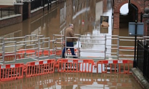 A man walks over a temporary bridge erected over flood water in York in the aftermath of Storm Dennis.