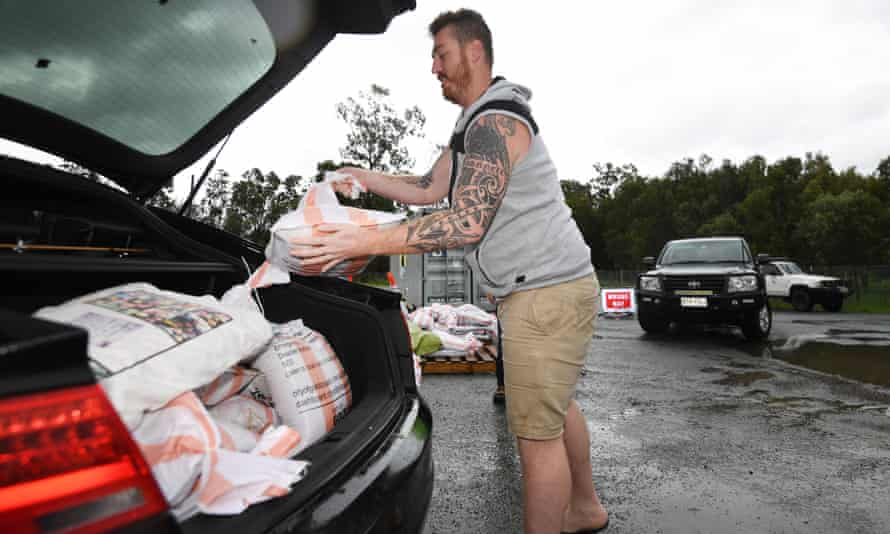 A man loads sandbags into his car on the Gold Coast on Sunday. Heavy rainfall, high winds and flooding is forecasted for south-east Queensland and into northern NSW.