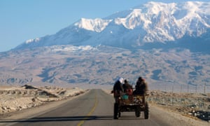 Passengers sit in an open topped vehicle on the Karakoram Highway,