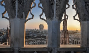 A view across Milan at sunset between arches on the Duomo terrace, Italy.