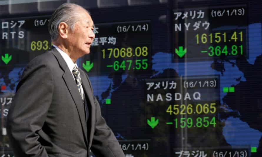 A man walks past a monitor displaying information of global markets at a securities branch office in Tokyo, Japan