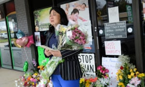 Ashley Zhang takes a moment before laying flowers at a makeshift memorial outside Youngs Asian Massage in Acworth, Georgia.
