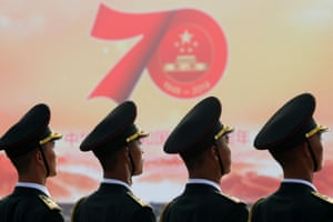 Soldiers of the People's Liberation Army in front of a sign marking the 70th anniversary of the founding of the People's Republic of China
