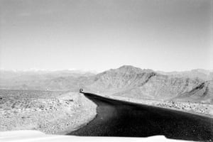 """Afghanistan, December 1966. A road stretching through unforgiving mountainous terrain. """"The road stretched black stretching over utterly desperate land that lay between thrusting ranges of intimidating rock that seemed cut off from anything that might have encouraged life. These stretches seemed to be filled with shrapnel left over from a war that the mountains were having with themselves."""""""