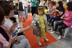 A child model posing at a fashion show