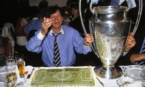 Raymond Goethals has one hand on the Champions League trophy and sits before a celebration cake
