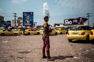 A man sells water at a taxi bay overlooked by campaign posters
