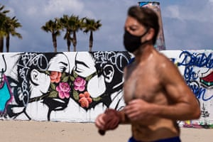 A man jogs past a mural showing a couple kissing with face masks next to the beach in Venice, Los Angeles county.