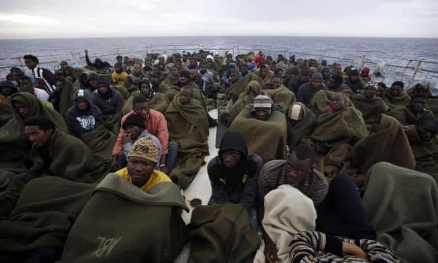 Migrants sit on the deck of the Belgian navy vessel Godetia
