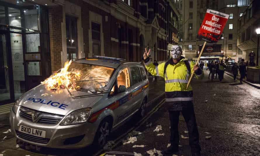 Protester next to burning police car