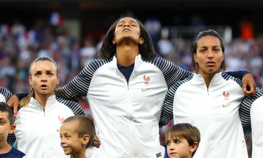 Marion Torrent, Wendie Renard, and Sarah Bouhaddi of France sing the national anthem prior to the group A match between France and Norway at Stade de Nice.