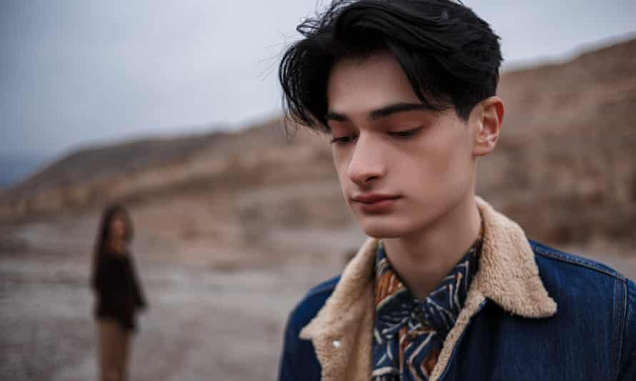 Dramatic portrait of a young brunette guy in cloudy weather. somewhere behind him, out of focus,is a woman