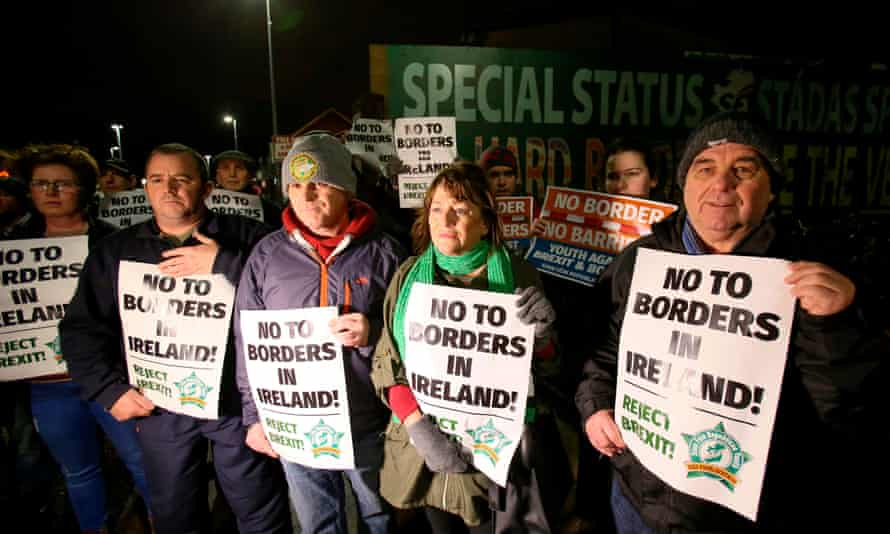'The bottom line is that the DUP cannot countenance any change that would involve border checks between Great Britain and Northern Ireland.'Protesters line a road holding placards near a new anti-Brexit mural, erected by Republican party Sinn Féin, in west Belfast.