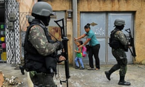 A mother and child walk past military police on patrol near the Vila Kennedy favela in Rio de Janeiro on February 23, 2018.