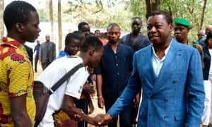 Togolese president Faure Gnassingbé shakes hands with voters at the polls.