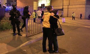 A man and woman hug on the streets of Manchester.