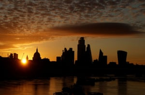 London, UK. The sun rises behind the skyline of St Paul's Cathedral and the City