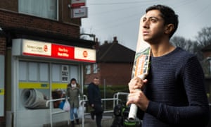 Hameed standing on a street in Bolton, holding a bat over his shoulder and staring up and ahead
