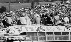 Fans sitting on top of a painted bus at Woodstock, 1969.